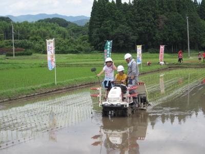 田んぼの所有者伊東さんに付き添われ田植え機体験乗車をする子どもたち