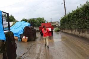 まだ土砂が残る中、組合員のもとへ荷物を運ぶ担当者