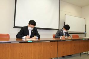 調印書にサインする(左)嶋田理事長(右)安田会長