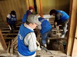 床下の泥を土嚢に詰める作業