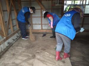 倉庫に入った泥をほうきではく作業